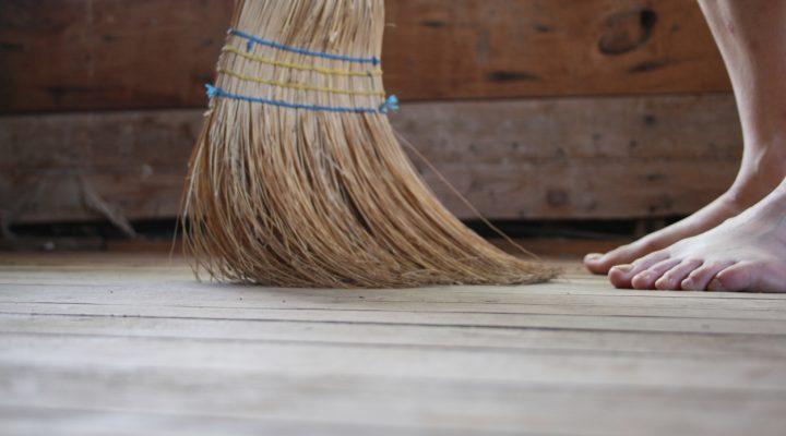A woman's bare feet and broom sweeping a hardwood floor.